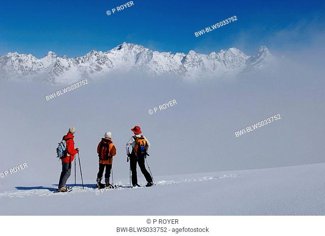 three persons with snow shoes enjoying panoramic view, France