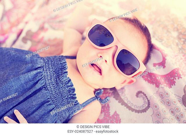 Portrait of adorable baby girl wearing sun glasses, vintage style warm color tone