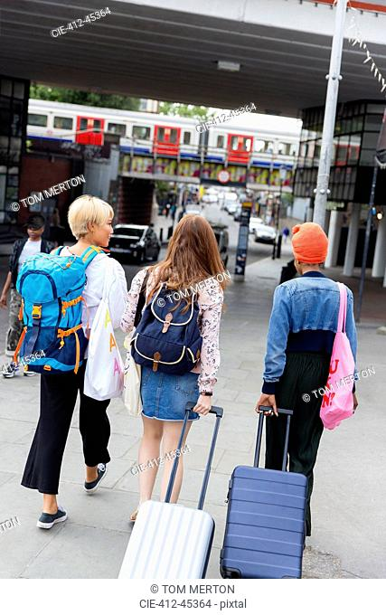 Young women friends with suitcases outside urban train station