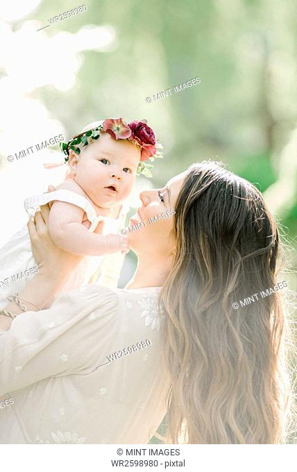 Portrait of a smiling mother and baby girl with a flower wreath on her head