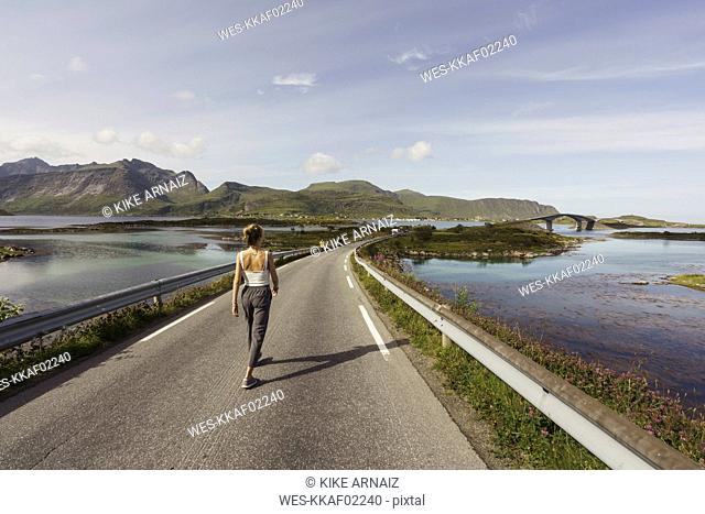 Young woman walking on an empty road, Lapland, Norway