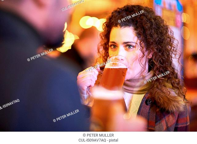 Young woman on night out drinking a glass of beer