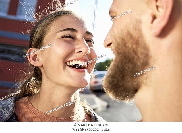 Portrait of laughing young woman face to face with her boyfriend