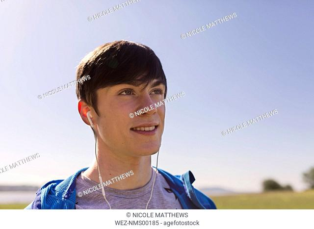 Portrait of young man hiking, listening to music