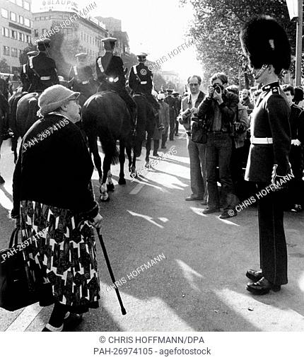 An elderly woman from Berlin (l) is puzzled as she watches the guard uniform with bearskin of a British soldier (r) during a military parade at Kurfuerstendamm...