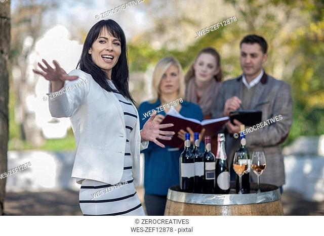 Wine saleswoman with group of clients outdoors