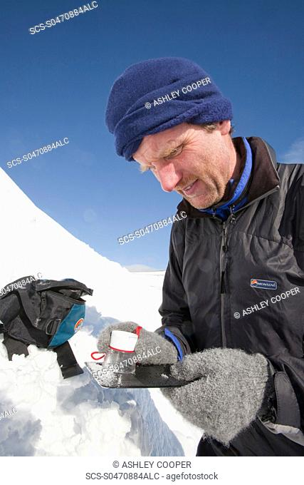 A member of the Scottish Avalanche Information Service looks at snow crystals to help assess avalanche risk on Cairngorm in the Cairngorm National Park in...