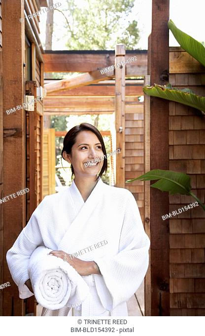 Hispanic woman in bathrobe carrying towel in spa