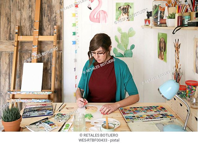 Woman painting aquarelle of a pineapple at desk in her studio