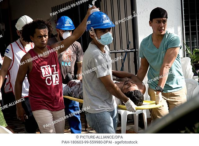 02 June 2018, Nicaragua, Masaya: Workers of the Red Cross taking care of an injured protestor at the demonstrations against the government