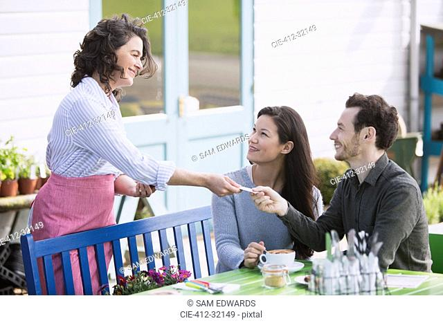 Couple paying waitress at outdoor cafe