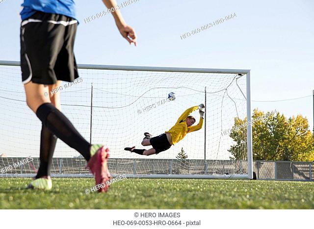 Soccer goalie attempting to stop soccer ball