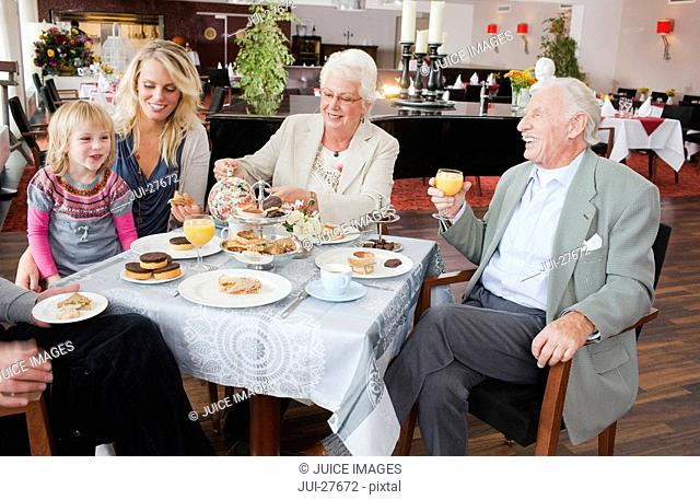 A three generation family having afternoon tea in a restaurant