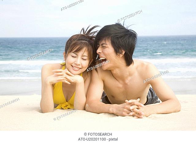 Japanese couple lying on a beach in swimsuit