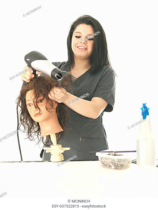 A pretty young cosmetology student laughing as she styles her practice mannequin's hair. On a white background