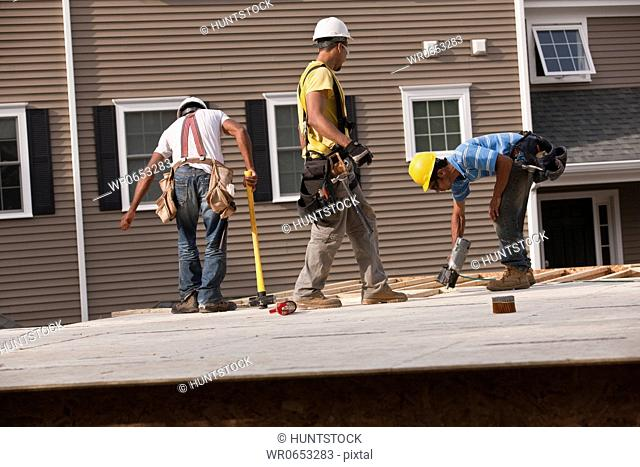 Carpenters installing particle board using a sledge hammer and a nail gun