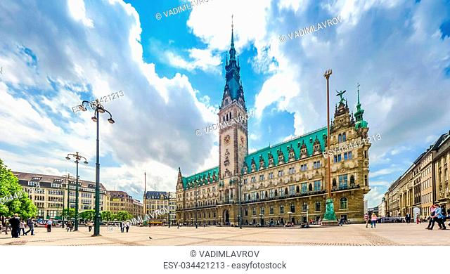 Beautiful view of famous Hamburg town hall with dramatic clouds and blue sky at market square near lake Binnenalster in Altstadt quarter, Hamburg, Germany