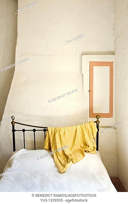 Cast iron framed bed with material draped over the bedstead in French country house near Nîmes in the south of France