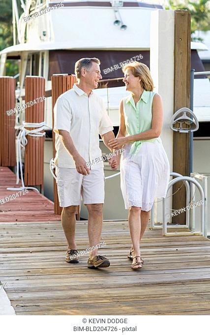 Caucasian couple walking on dock