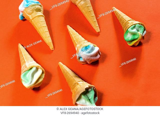 Sugar candy cones on an orange background, topped with frosted candy