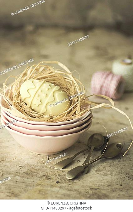 A white chocolate egg in an Easter nest