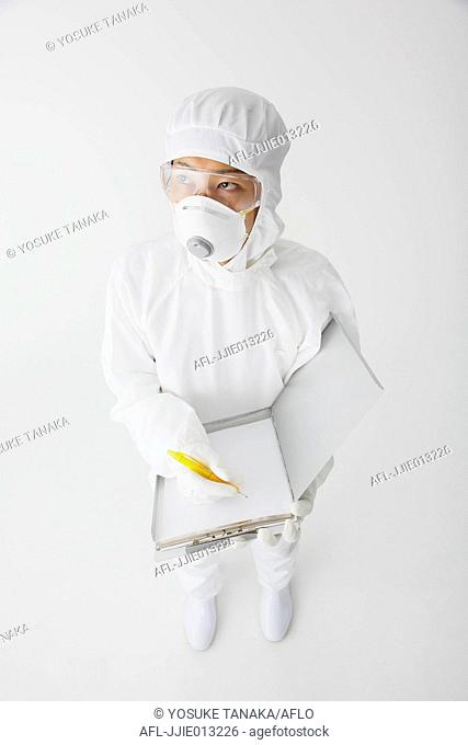 Young Japanese man in a protective suit taking notes