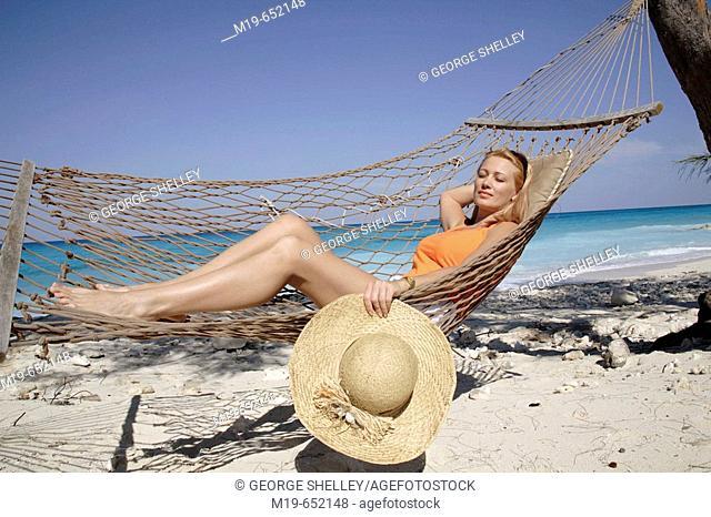Girl relaxing in a beach hammock