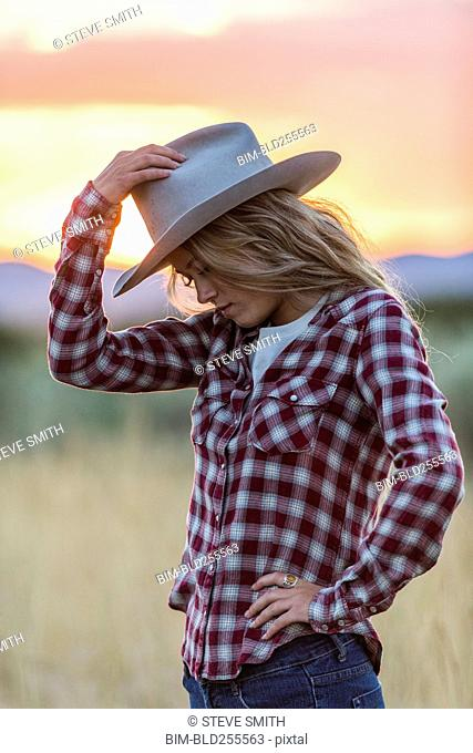 Caucasian teenage girl wearing cowboy hat at sunset