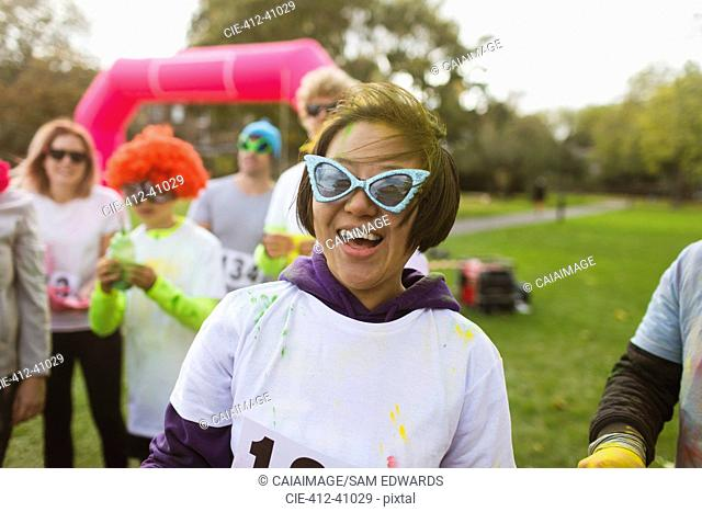 Portrait playful female runner in silly sunglasses at charity run in park