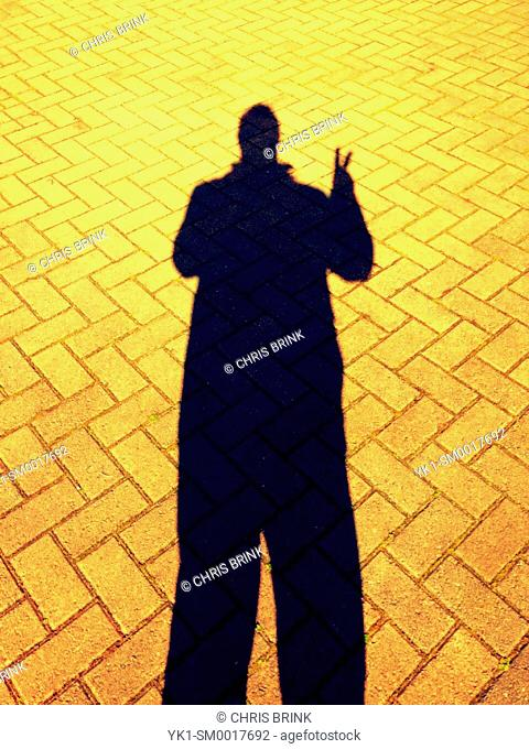 Person shadow on pavement showing V sign