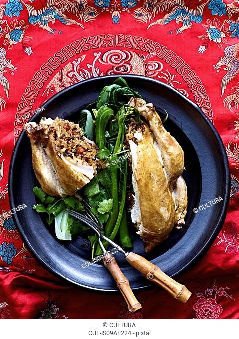 Still life of Beggars Chicken with lotus leaf and greens