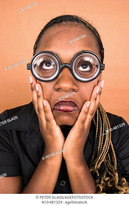 Young black woman, with her hands on her face, wearing thick toy glasses