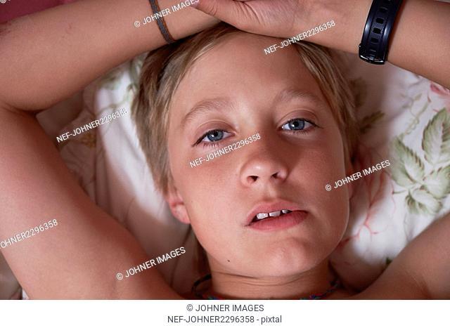 Portrait of boy lying in bed