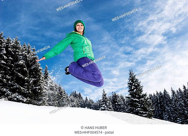 Austria, Salzburg, Portrait of young woman jumping in snow, smiling