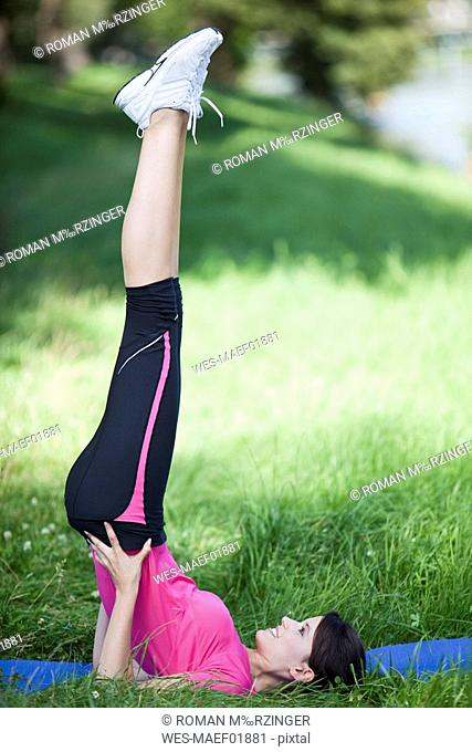 Germany, Bavaria, Woman in yoga shoulder stand, outdoor