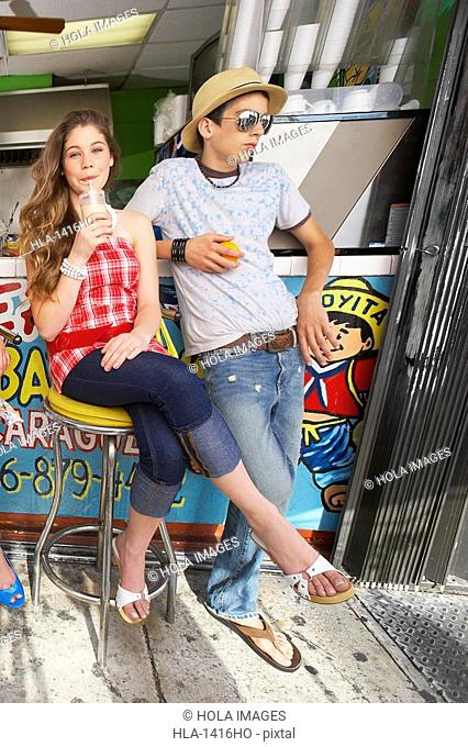Teenage girl drinking juice with a teenage boy standing beside her