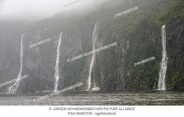 A ship with tourists drives close to the huge waterfalls along the Milford Sound cliff. (24 January 2016) | usage worldwide