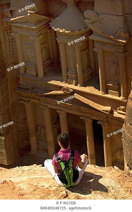 young backpacker sitting on a rock spur looking at the porch of the rock cut tomb called 'treasury' Al Khazneh of the historical rock cut city of Petra, Jordan