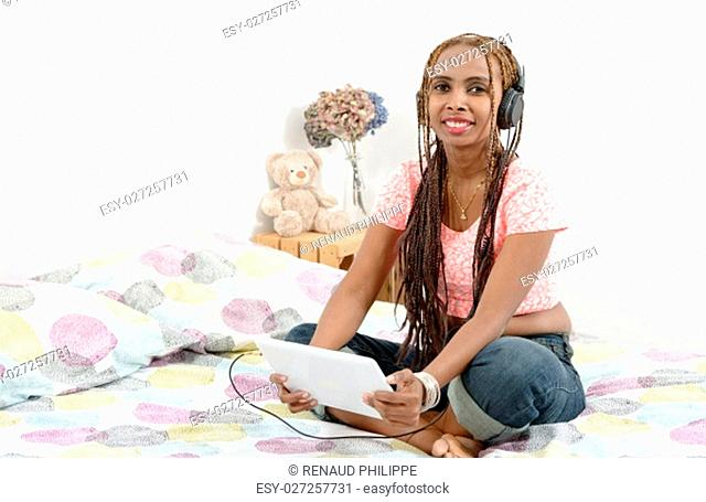 Beautiful young african american woman with braids using tablet computer