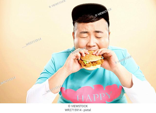 Little fat man eating hamburgers