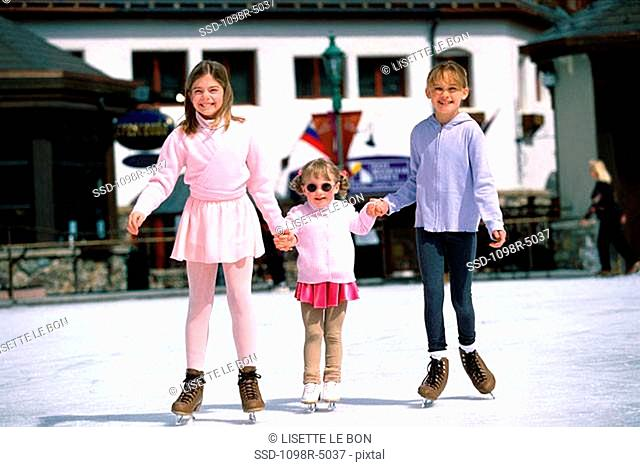 Portrait of three children holding hands ice skating