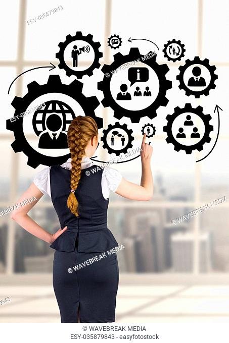 Business woman interacting with people in cogs graphics against office background