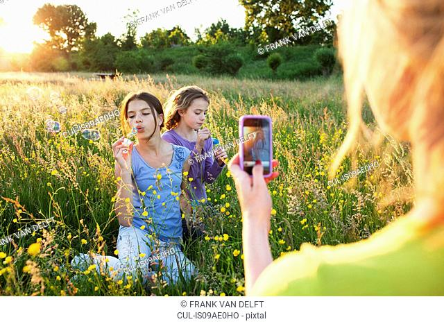 Mother taking photograph of girls blowing bubbles