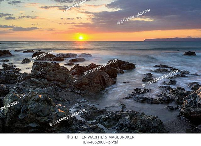 Sunset on the Pacific coast, water washing over rocks, Osa Peninsula at the rear, Golfo Dulce, Puntarenas Province, Costa Rica
