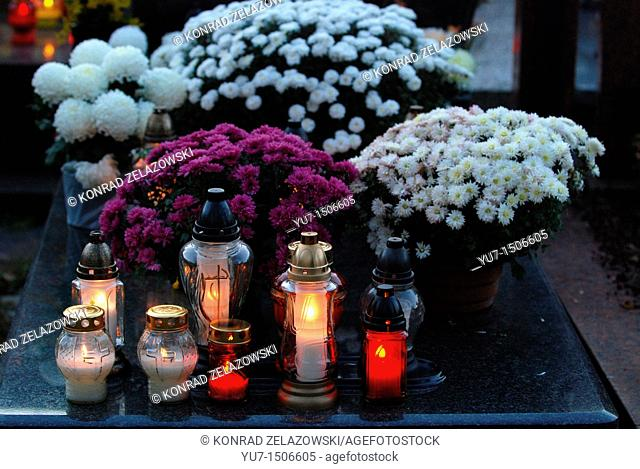 Chrysanthemums and candles on Wolski cemetery in Warsaw, Poland during All Saints Day