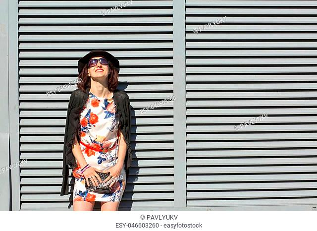 Cheerful brunette woman wearing stylish hat and sunglasses, posing near the shutters at the street. Space for text