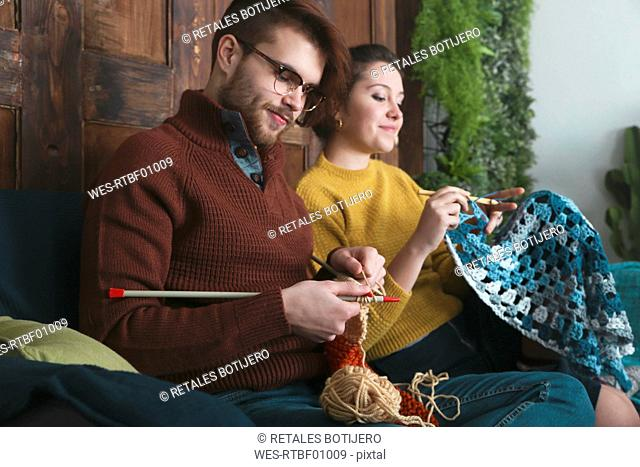 Young couple knitting and crocheting in living room