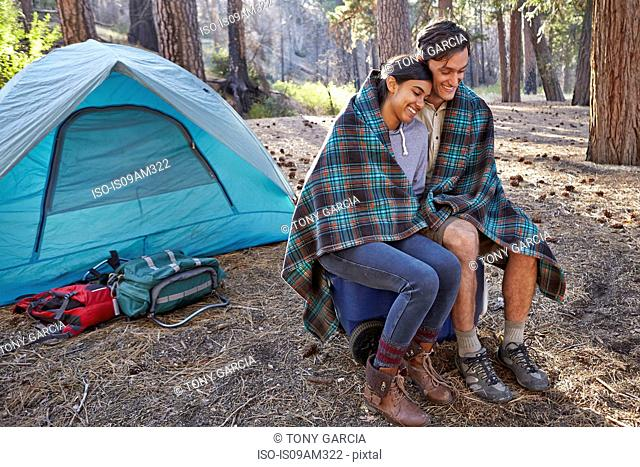 Young camping couple wrapped in blanket in forest, Los Angeles, California, USA