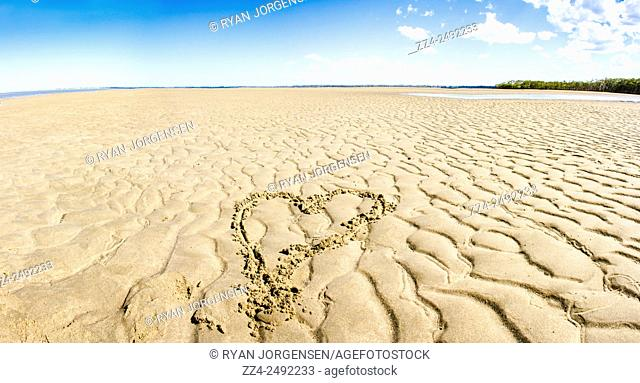 Combined image photostitch of a heart written in the sand of an Australian beach landscape; taken Deception Bay; Queensland. Ocean love