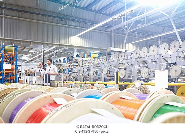 Male supervisor and worker checking inventory behind multicolor spools in fiber optics factory